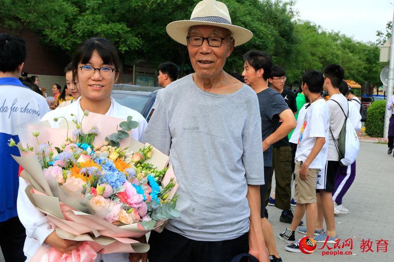 老爺爺早早來到考點前等候,第一時間為孫女送上一大束鮮花。李依環 攝